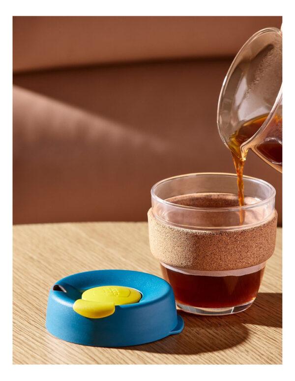 Beber chá em copo reutilizável de vidro, com tampa e banda de cortiça